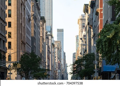 View down Fifth Avenue in Manhattan, New York City with historic buildings lining both sides of the street in NYC