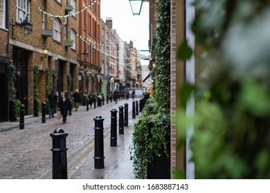 A view down Floral Street in Covent Garden, London with green foliage in the foreground