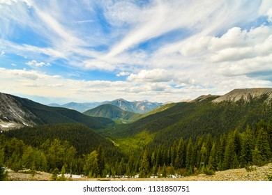 The view down into a forest valley from a mountain summit in Spring - Canadian Rocky Mountains, Pedley Pass, British Columbia, Canada