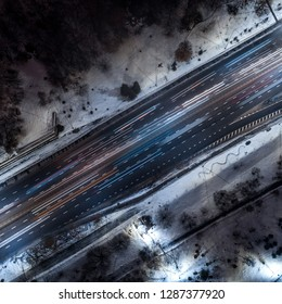 View down the night highway illuminated from cars and street lights. Romantic night aerial photo of cars traveling on the road in winter.