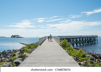 A view down the pier boardwalk on a beautiful summer day by the Long Island Sound at Calf Pasture Beach in Norwalk, Connecticut USA