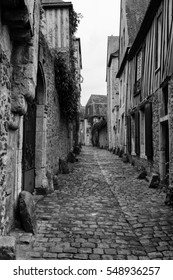 View down a quiet narrow cobbled street in France with timber-framed houses on both sides