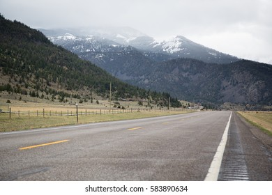 View down a rural two lane country road with cattle fence and yellow grass in late winter outside of Yellowstone National Park with snowy hills in background