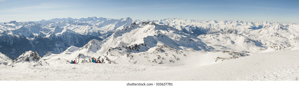 View down a snowy piste with skiers relaxing and view over mountain valley