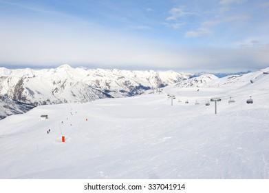 View down a snowy ski piste in alpine mountain valley