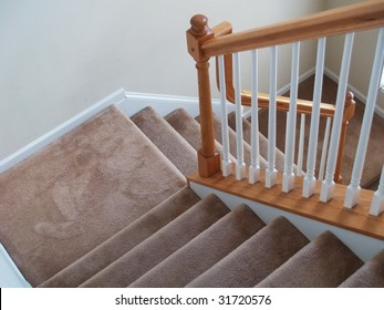 A view down a stairway in a modern american home. Carpeted stairs and a wooden banister and railing are visible