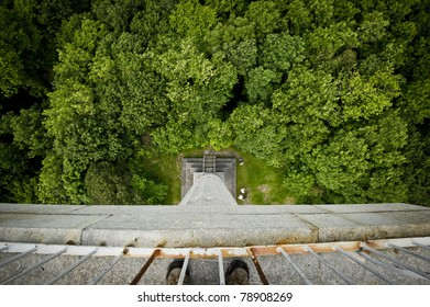 View down in to trees from a tall tower with a pair of feet.
