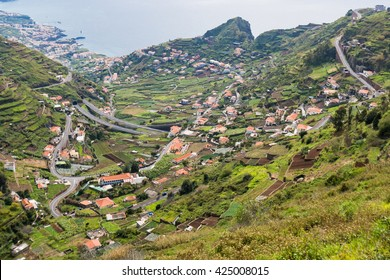 View down valley in Madeira Portugal.  High angle view down hillside into green valley with houses and roads in Madeira Portugal