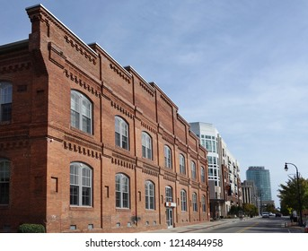 View of downtown Durham showing a former tobacco warehouse converted into loft style apartments, with newer buildings in the background