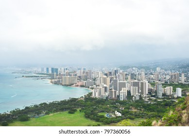 view of downtown Honolulu and Waikiki from Diamond Head Crater Summit Hawaii, in a rainy, dramatic day