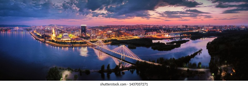 view of the downtown Krasnoyarsk, the bridge through the Yenisei River a sunset, shooting from air