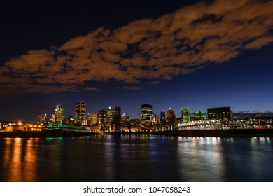 View of downtown Montreal, Canada at night, with St-Lawrence river in the foregound.
