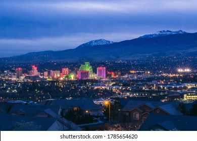 View of downtown Reno, NV at dusk with the Sierra Nevada Mountains in the background.