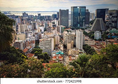 View of Downtown Rio De Janeiro at Sunset with Cathedral, Skyscrapers, and Bridge. Framed by Trees.