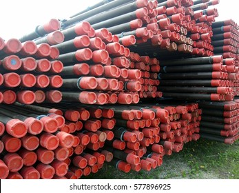 View of drilling pipes casing and tubing stacked at open yard of oil and gas warehouse