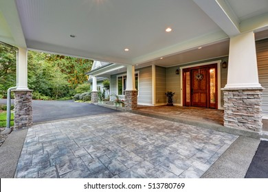 View of driveway with an all weather covered entry. White columns with natural stone trim. Northwest, USA