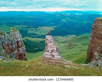 View from the drone from the air. Man stands on a rock in the amphitheater on the plateau Bermamyt North Caucasus at sunrise.
