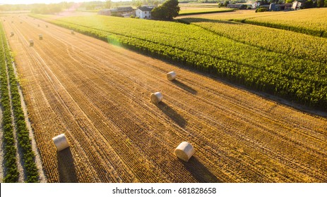 a view from drone of hay bales on field in italian countryside in back light photography at sun rise