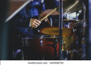 View of drum set kit on a stage during jazz rock show performance, with band performing in the background, drummer point
