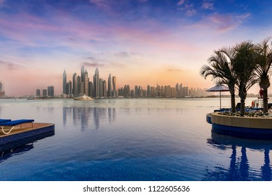 View to the Dubai Marina skyline with a swimming pool in front during sunset time
