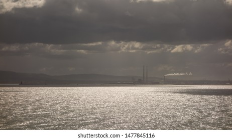 A view of Dublin Bay from the cliffs at Red Rock, Sutton, County Dublin, Ireland. The twin towers of Poolbeg power station can be seen in the distance.