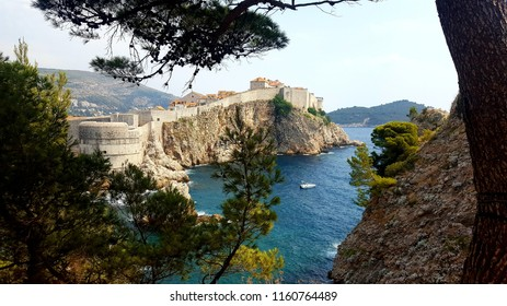 View of Dubrovnik, Croatia, through the treeside. Rockface visable supporting Dubrovnik by the ocean