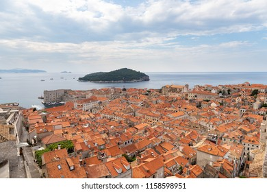 View of Dubrovnik Old Town, Red roof houses, port and Lokrum Island.