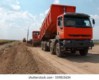 View of dump truck dumping earth