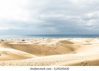 View of Dunes in Maspalomas, Canarias islands, Spain. Yellow and golden sand from Sahara desert and distance view of blue Atlantic ocean and beach.