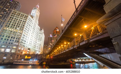 View of Dusable bridge and Tribune Tower at night along with Chicago Riverwalk.