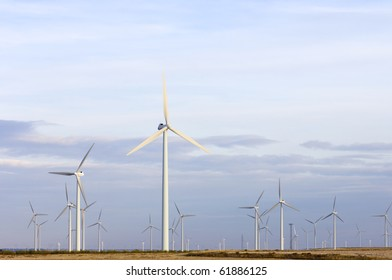 view at dusk of a group of modern windmills for electricity production