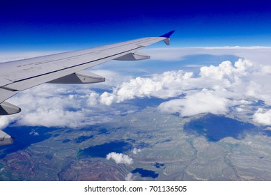 View of Earth from an airplane with the plane wing, blue sky, clouds, and rugged landscape