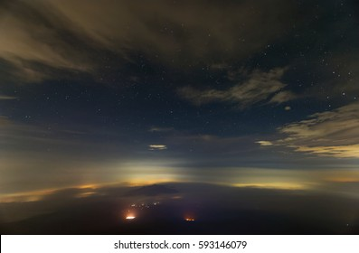 A view of earth atmosphere at night. Long exposure photography. The landscape shrouded in fast moving fog and clouds. Some star constellations can be seen through the clouds in the sky at night.