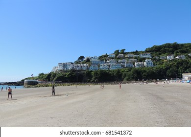 A view of east Looe beach in Cornwall, with holidaymakers enjoying the stunning blue skies and sunshine on the sands, and the sea.  West Looe can be seen in the background
