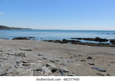 A view from east Looe beach over the rocks, looking east from Cornwall towards the Rame head peninsular and Plymouth in Devon