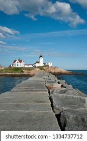 View of Eastern Point lighthouse from stone jetty in Gloucester, Massachusetts, on a warm summer day.