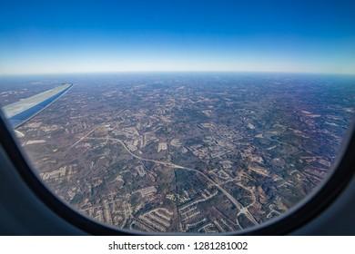 View of eath and blue sky horizon through airplane porthole