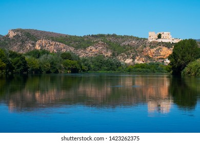 a view of the Ebro River as it passes through Miravet, Spain, highlighting its Templar castle in the top of the hill