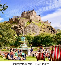 View of Edinburgh castle from Princes street gardens, popular outdoor park and tourist attraction in the city centre. Edinburgh Scotland UK. AUGUST 2018