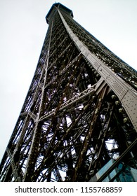 A view of the Eiffel Tower from below looking up, so that the tower soars agaisnt a cloudy sky.