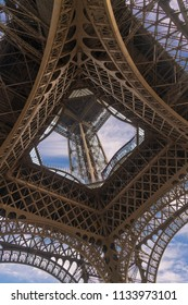 View of Eiffel Tower from the Ground Looking Up Through the Metal Steel Structure and Blue sky and Clouds.
