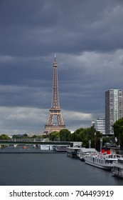 """View of the Eiffel tower from the port of Javel, august 2017 18th. You can also see the Beaugrenelle shopping center, and the boats on the river """"La Seine""""."""