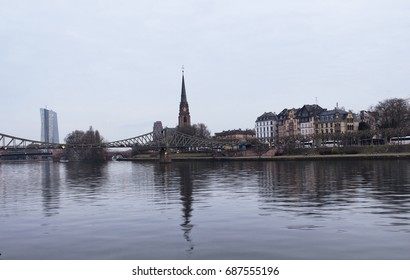 View of Eiserner Steg bridge and Dreikonigskirche Protestant Church by main river in Frankfurt.