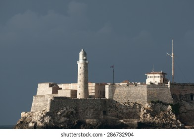 View of el Morro Castle lighthouse architecture in dramatic sunset light against dark cloudy sky