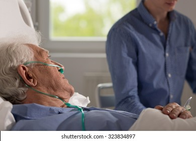 View of elder sick man being visited by his realtive