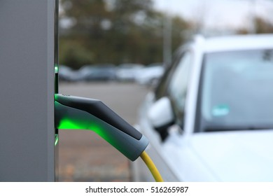 View from an Electric Car Charging Column and in the background a partial view of a white car