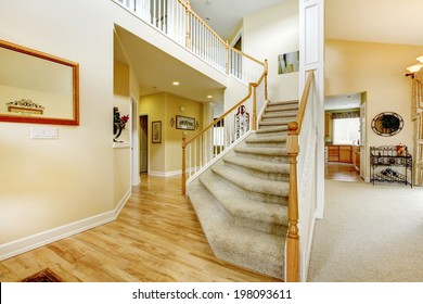 View of elegant staircase with wooden white and brown railings in modern large house
