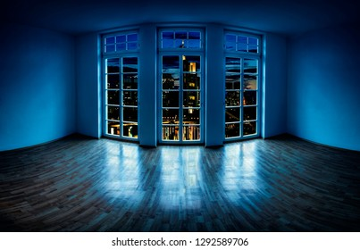 View from an empty apartment through a large window to a lit city at night