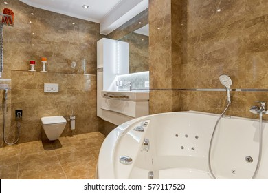 View of empty bathroom in brown and white colors with rounded ceramic bath,  bowl and other accessories, brown floor and big mirror.