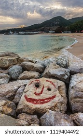 View of an empty beach with a smiling face painted on a stone in a overcast day